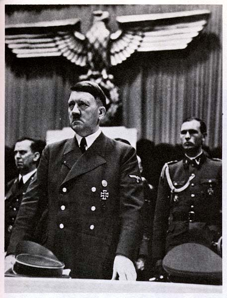 Hitler standing under the Eagle of the Third Reich.