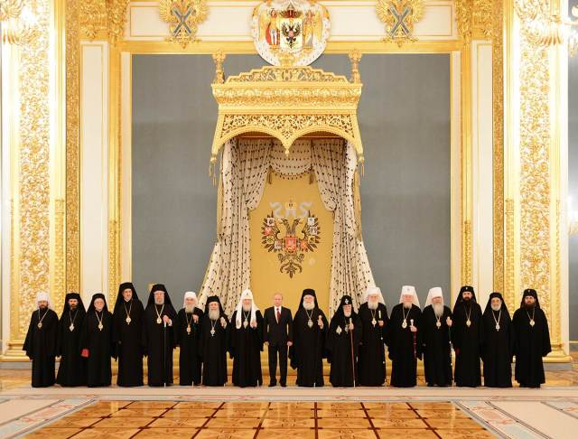 Putin standing under the Double Headed Eagle with members of the Russian Orthodox Church